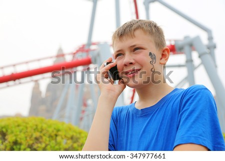 Cute boy talking on a cell phone at an amusement park. Drawing a dragon on her cheek.