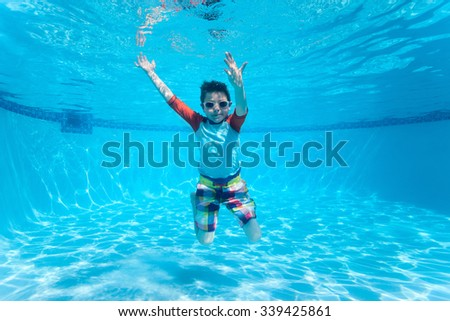 Cute boy underwater in swimming pool - stock photo