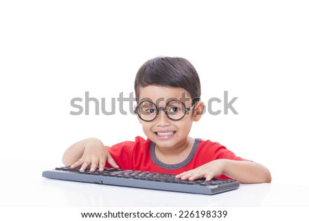Cute Boy using a keyboard  - stock photo