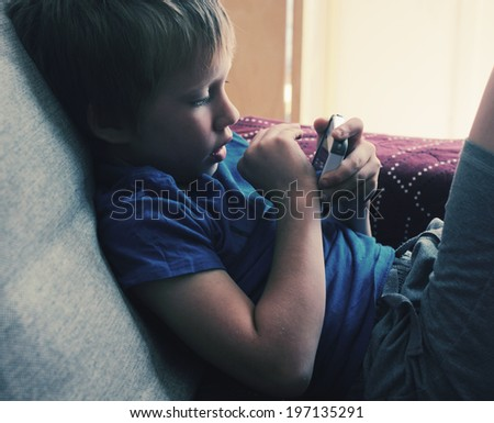 Cute boy using a mobile phone - stock photo