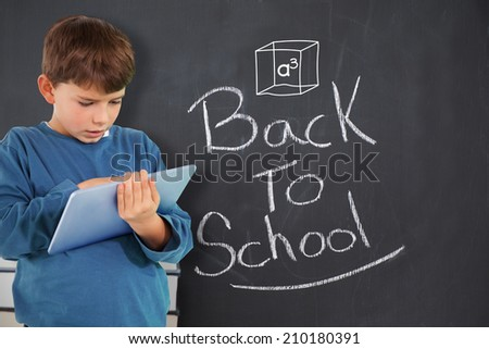 Cute boy using tablet against back to school message on chalkboard