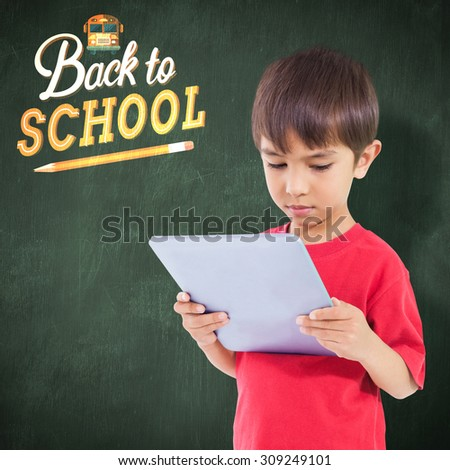Cute boy using tablet against green chalkboard