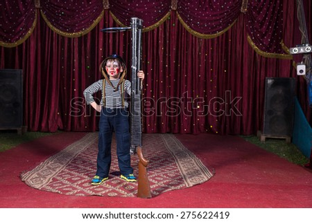 Cute boy wearing vintage helmet and clown make up while acting and posing as a proud soldier who holds a huge upright riffle - stock photo