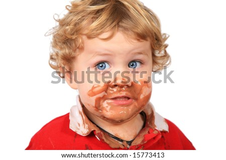 Cute boy with chocolate ice cream on face