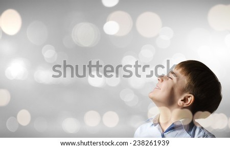 Cute boy with closed eyes against bokeh background - stock photo