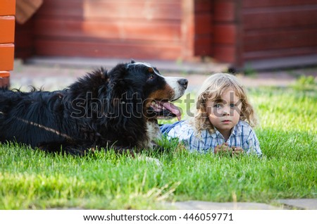 cute boy with curly blonde hair lying on grass with bernese mountain dog