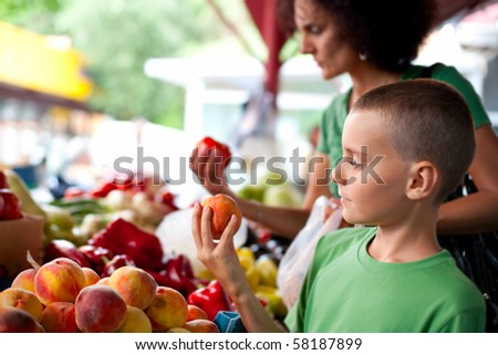 Cute boy with his mother buying fresh vegetables at the farmer's market - stock photo