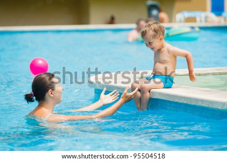Cute boy with his mother playing in a pool of water during the summer