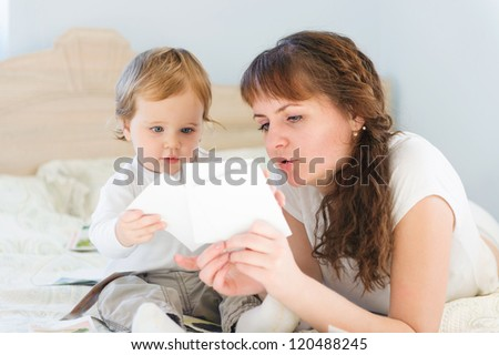 Cute boy with his mother playing with paper cards - stock photo