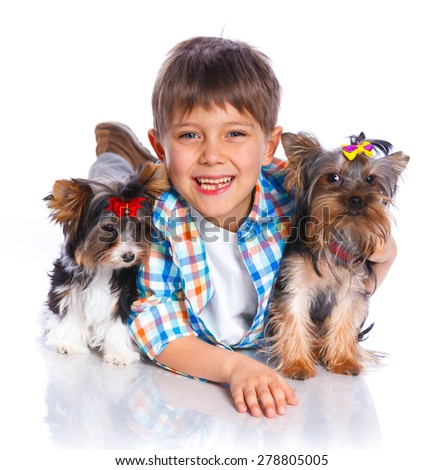 Cute boy with his two Yorkshire terrier smiling at camera on isolated white background