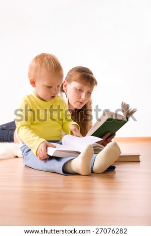 Cute boy with mother reading a book at home - stock photo