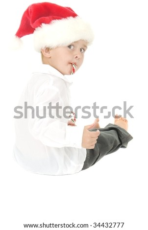 Cute Boy with Santa hat has candy cane in mouth and handful of Candy canes - stock photo