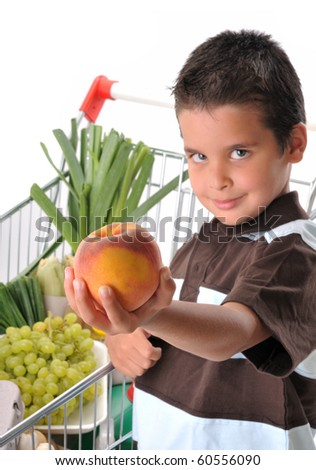 Cute boy with shopping trolley isolated on white - shallow DOF, focused on peach. - stock photo