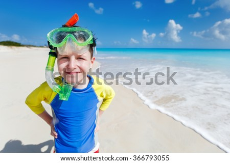 Cute boy with snorkeling equipment at tropical beach enjoying summer vacation
