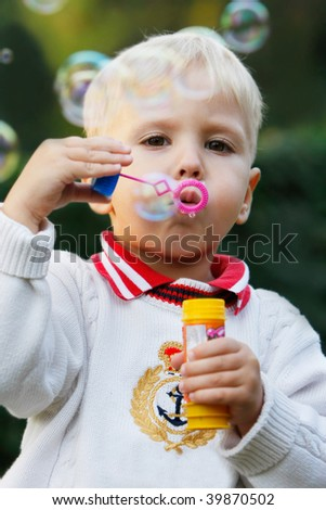 cute boy with soap bubbles on natural background