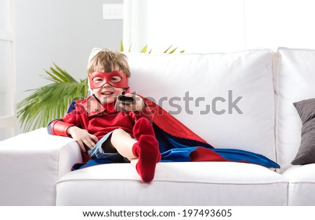 Cute boy with super hero costume sitting on living room sofa and watching tv. - stock photo