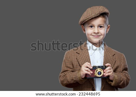 Cute boy with vintage photo camera on the grey background.  - stock photo