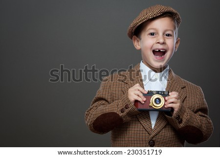Cute boy with vintage photo camera on the grey background. ( Retro style.) - stock photo