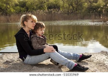 Cute boy with woman sitting near a lake - stock photo