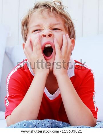 Cute boy yawning - stock photo