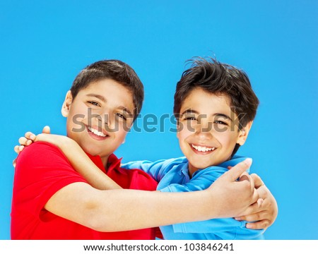 Cute boys smiling over blue sky, preteens playing outdoor, kids holding hands, best friends hug, beautiful children having fun, happy brothers, family joy and happiness concept - stock photo