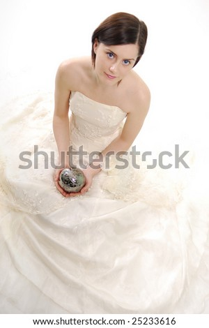 Cute bride holding on her lap a magic silver ball in a high key light - stock photo