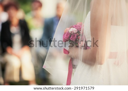 Cute bride in a white dress holding a wedding bouquet before - stock photo