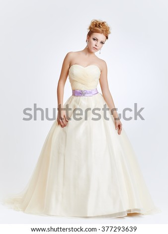 Cute bride in long dress posing against a light background - stock photo