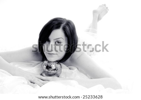 Cute bride resting her head on a silver magic ball, high key isolated on white - stock photo