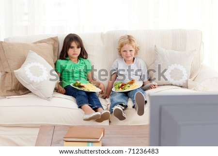 Cute brother and sister having dinner on the sofa in front of the television - stock photo