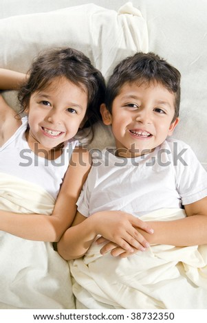 Cute brother and sister laying in bed - stock photo