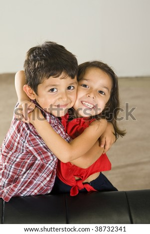 Cute brother and sister sitting on a couch - stock photo