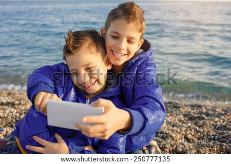 Cute brothers laughing while taking selfie photos with smart phone at beach near the sea - stock photo