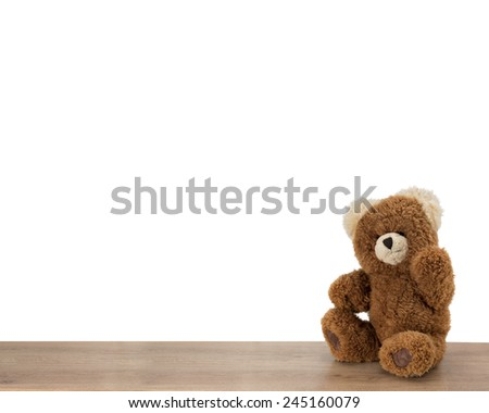 Cute brown teddy bear sitting and waves on a wooden table against pure white background. With space for text etc. - stock photo