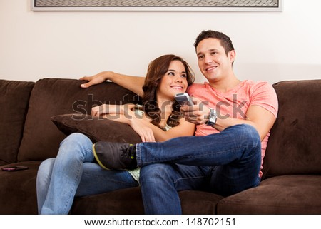 Cute brunette and her boyfriend relaxing on the couch and watching some TV - stock photo