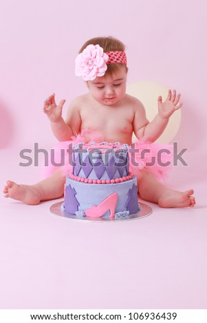 Cute brunette baby girl in pink tutu and flower head band sitting on pink background looking at her birthday party double tier pink and purple butter iced cake with hands in air happy and excited