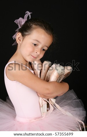 Cute brunette ballet girl holding lots of pointe shoes - stock photo