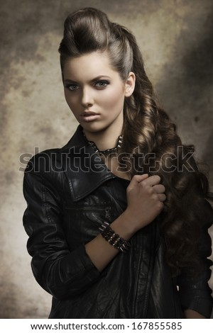 cute brunette female posing in fashion shoot with dark style, casual leather jacket, rock accessories and long wavy hair.   - stock photo