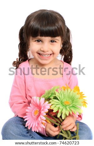 Cute brunette four year old girl smiling and holding colorful daisies on a white background - stock photo