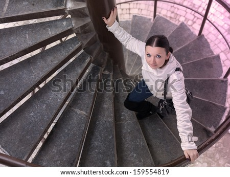 cute brunette girl climbs the ladder - stock photo