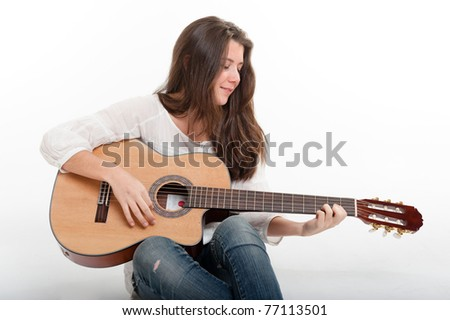 Cute brunette girl playing the guitar - stock photo
