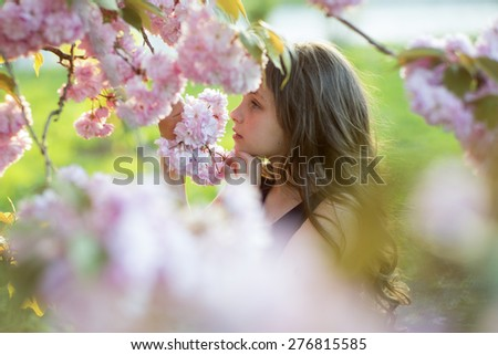 Cute brunette girl smelling flowers standing amid pink japanese cherry blossom in broad daylight in the park copyspace, horizontal picture - stock photo