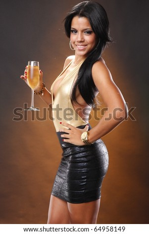 Cute brunette in black skirt and gold leotard holding wine flute - stock photo