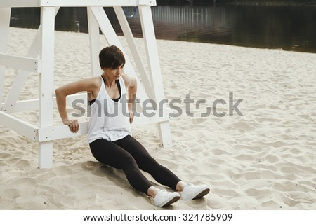 cute brunette in black sport outfit does stretching near white wooden judgment seat for beach volleyball on autumn river beach. She is in leggings, top and white sneakers. Sun shines. Clouds in sky. - stock photo