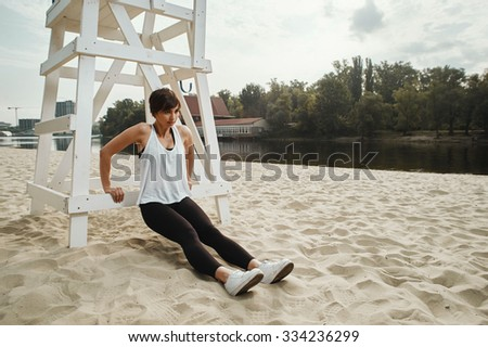 cute brunette in black sport outfit does stretching near white wooden judgment seat for beach volleyball on autumn river beach. She is in leggings, top and white sneakers. Sun shines. Clouds in sky.