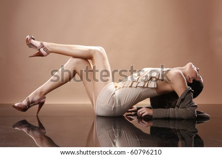 Cute brunette in earthy outfit on mirrored floor - stock photo