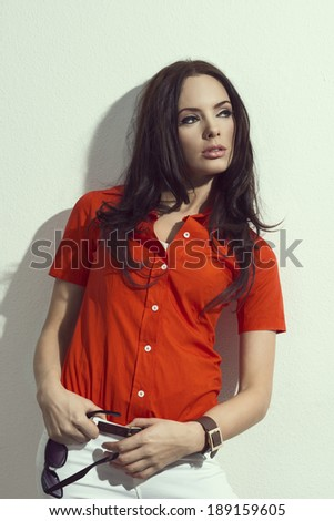 cute brunette in red shirt with sunglasses against a white wall in summer day - stock photo