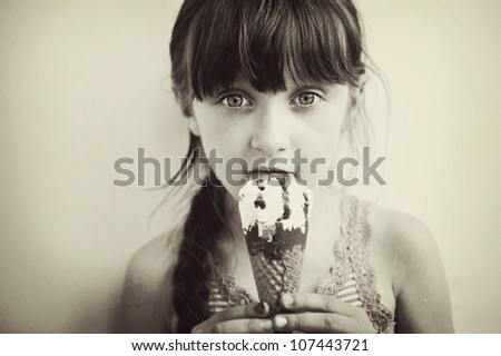 Cute brunette little girl eating ice cream, retro style, artistic noise added - stock photo