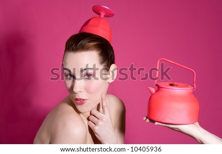 Cute brunette looking funny with a kettle next to her - stock photo