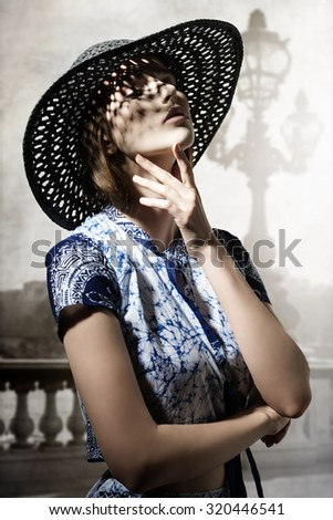 cute brunette model with elegant hat and shirt in expressive fashion pose.